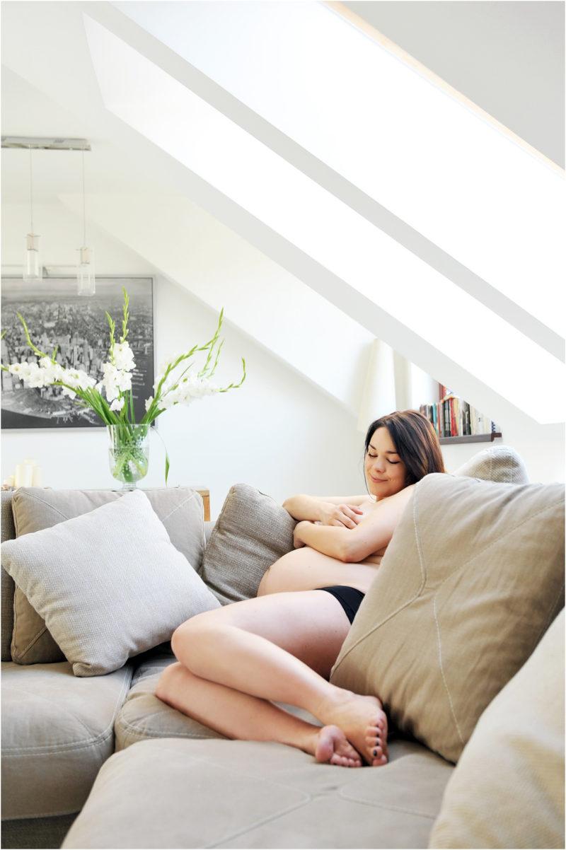 młoda piękna kobieta pozuje na kanapie do zdjęcia sesja ciążowa